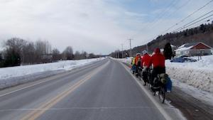 On voit une route dans la partie gauche de l'écran et des cyclistes qui se suivent en rang sur la partie droite de la route. C'est l'hiver.
