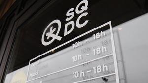 La porte d'une succursale de la SQDC, sur laquelle sont affichées les heures d'ouverture.