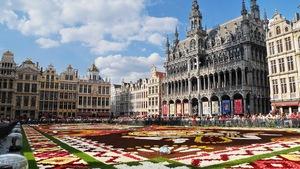 Un parterre fleuri en forme de motifs savamment exécuté occupe le centre de la place. Des bâtiments à l'architecture raffinée se dressent autour.