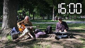 Deux hommes assis au pied d'un arbre dans un parc jouent de la guitare et du clavier.