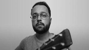 Photo noir et blanc : l'auteur-compositeur-interprète Jeffrey Piton tient un guitare (la tête de celle-ci est à l'avant plan, un peu fou).