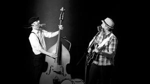 Photo noir et blanc. Les deux membres de la formation Fins Renards en spectacle. L'un à la contrebasse et l'autre à la guitare.