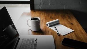 On y voit un ordinateur portable, une tasse de café, un carnet de notes et un cellulaire sur un bureau de travail.