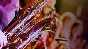 Un saxophone dans un éclairage chaleureux, rose et violacé
