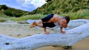 Andréann Duquet, faisant de l'acro-yoga sur un tronc d'arbre, sur une plage