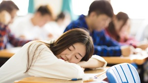 Une étudiante dort sur son pupitre pendant un cours.