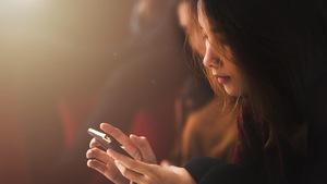 Gros plan sur une jeune femme asiatique, téléphone en main.