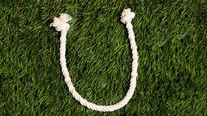 Une lettre faite de cordes nouées est déposée sur du gazon.