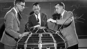 Trois scientifiques en veston observent et touchent au satellite Alouette 1, en 1961.