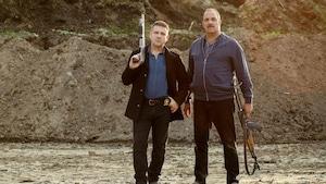 Les deux hommes tiennent un fusil dans la main.