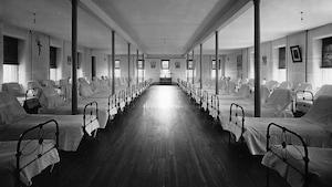 Photo en noir et blanc montrant plusieurs rangées de lits vides recouverts de draps blancs, et un crucifix sur le mur.
