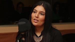 Aula Sabra derrière un micro dans un studio radio de Radio-Canada