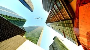 Un avion traverse le ciel au milieu des tours à bureaux.