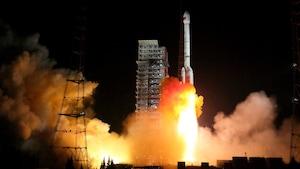 Une fusée dégage de grandes flammes orange lors d'un décollage de nuit.