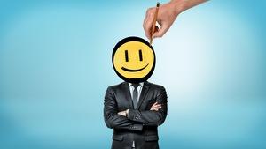 Un homme d'affaires dont la tête est redessinée pour ressembler à un « bonhomme sourire ».