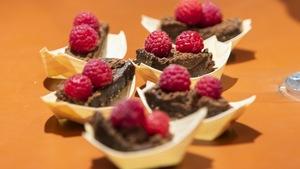 Des brownies véganes, décorés de framboises et servis dans de petites barquettes de carton.