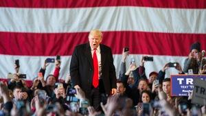 Donald Trump harangue la foule lors d'un événement électoral, devant un immense drapeau américain.