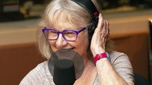 Une femme sourit devant un micro en tenant un écouteur de sa main gauche.
