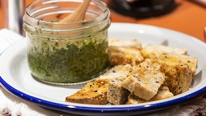 Un petit pot de pesto aux fanes de carottes posé sur une assiette, à côté de croûtons.