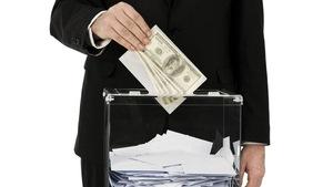 Un homme met un bulletin de vote et de l'argent dans une boîte.