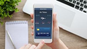 Un consommateur procède à l'achat de billets d'avion en ligne sur son téléphone intelligent.