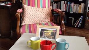 Au premier plan, une table basse, des tasses et un livre, un fauteuil devant des rayons de bouquins.