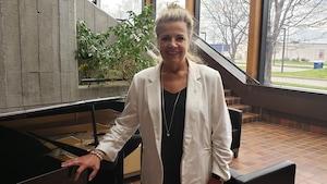 Brigitte Deschênes à côté d'un piano