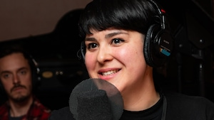 L'artiste aux cheveux noirs sourit à l'animatrice.
