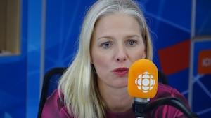 Catherine McKenna, une femme blonde aux yeux bleus, parle au micro orange d'Ici Premiere.