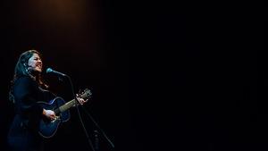 une chanteuse joue de la guitare sur scène
