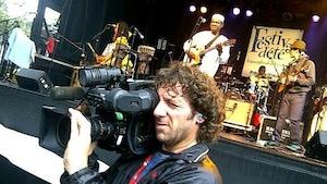 Daniel Beauparlant, caméra à l'épaule, devant la scène extérieure du Festival d'été de Vancouver.