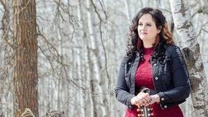 Une femme avec sa guitare dans les bois.