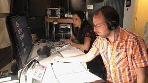 """Deux interprètes dans les coulisses du théâtre, regardent l'ordinateur pendant la pièce """"Ce que l'on attend de moi""""."""