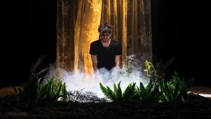 Un homme à genoux au milieu de la scène regarde de la fumée s'échapper d'un trou bordé de plantes.