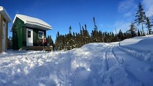Sentiers enneigés du Centre de plein air de la Minganie (on aperçoit deux petites cabanes avec un skieur)