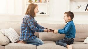 Un frère et une soeur se battent pour avoir le contrôle de la télécommande.