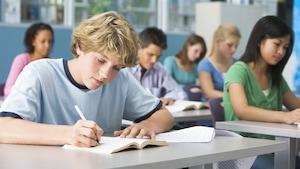 Des élèves du secondaire assis en classe. Au premier plan, un jeune lit et prend des notes.