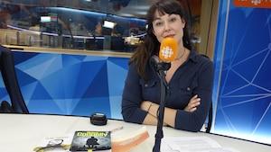 Une femme présente trois livres à la caméra, les bras croisés devant un micro orange dans un studio de radio.