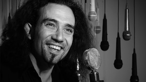 Le chanteur souriant Clément Courtois en gros plan devant un microphone avec en arrière plan des microphones suspendus du plafond.