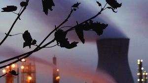 Photo de centrale thermique, en avant-plan, des feuilles mortes dans un arbre.
