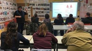 On voit des adultes assis dans une salle de classe avec plusieurs affiches écrites en micmac