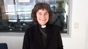 Une femme prêtre anglicane pose dans un studio de radio avec un grand sourire.