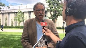 Le professeur Daniel Pauly est à l'extérieur devant un micro en entrevue avec Arnaud Decroix.