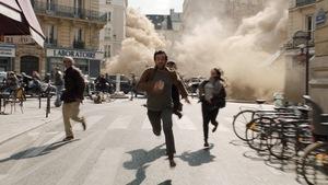 Une scène du film Dans la brume où on voit Romain Duris courir dans une rue de Paris pour fuir une brume épaisse.