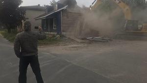 Arthur Fortin (de dos) filme les derniers moments de sa petite maison bleue, sous le pic des démolisseurs.