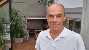 Denis Trottier dans l'entrée de la maison de Radio-Canada à Saguenay.