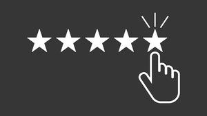Une ligne de cinq étoiles sur fond noir, avec une main sélectionnant la cinquième, pour représenter le travail de la critique.