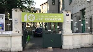 L'entrée d'une cour arrière d'un édifice avec une bannière sur lequel il est écrit les 10 ans du Centre communautaire juif de Cracovie