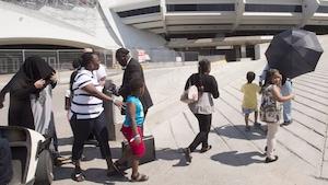 Des demandeurs d'asile arrivent au stade olympique