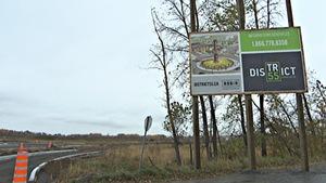Une pancarte du nouveau projet du quartier District 55 à Trois-Rivières devant le terrain où sera construit le nouveau Colisée